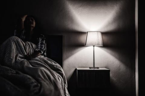 black and white image of woman depressed and alone shut in her bedroom